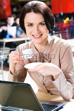 Деловая женщина сидит в кафе с чашкой кофе в руках и с ноутбуком рядом