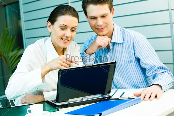 Деловые партнеры сидят за столом и обсуждают работу