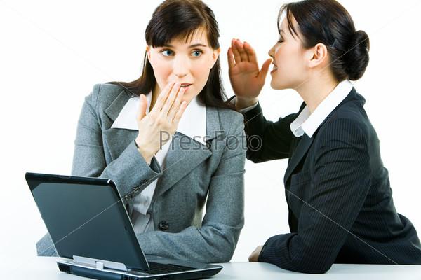 Деловая женщина делится секретом с другой на работе