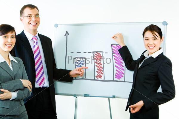 Деловые партнеры стоят у доски с нарисованными графиками