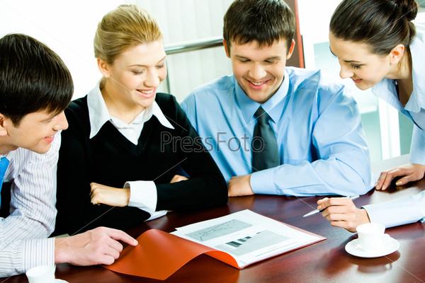 деловые партнеры за столом смотрят в документ