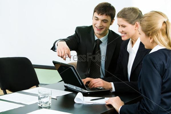 Деловая группа сидит за столом и смотрит на экран ноутбука