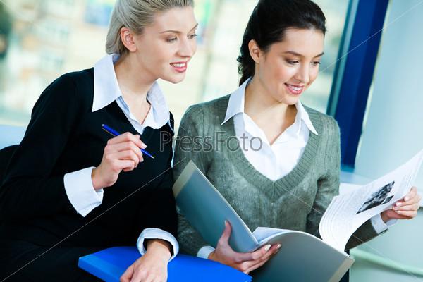 Две деловые женщины сидят в офисе и работают с документами