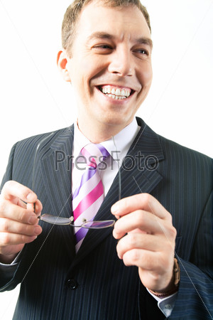 Portrait of happy businessman looking aside with glasses in hands