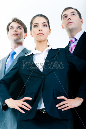 Portrait of three confident business partners looking forward with serious faces
