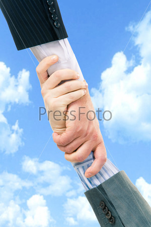 Vertical image of business trust of two partners on the background of sky