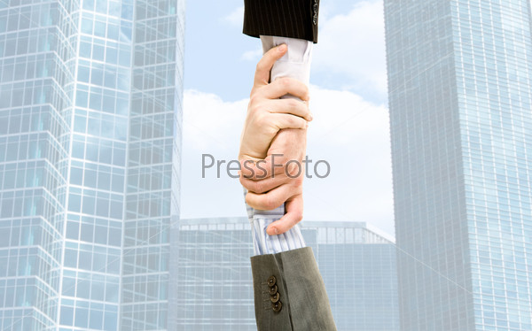 Handshake of businesspeople on the background of the modern building