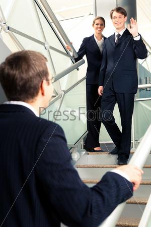 Деловые смотрят друг на друга и приветствуют на лестнице