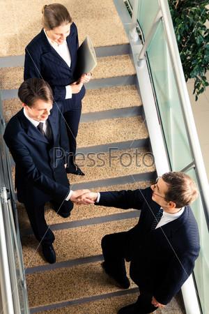 Рукопожатие деловых партнеров на лестнице в офисном здании