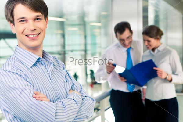 Бизнесмен смотрит в камеру с улыбкой в рабочей обстановке
