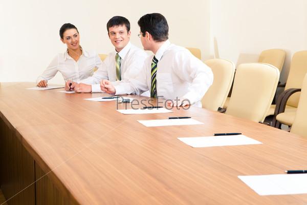 Трое деловых партнеров обсуждают рабочие идеи за столом в офисе