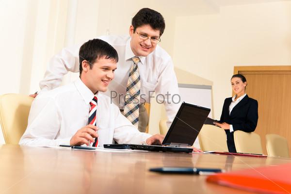 Двое мужчин смотрят на экран ноутбука на фоне секретаря