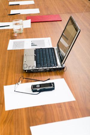 Рабоччее место с ноутбуком, несколькими бумагами, ручками и стаканом воды
