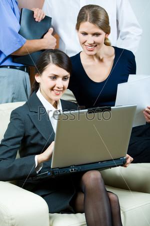 Фотография на тему Элегантная деловая женщина сидит с ноутбуком и смотрит на его монитор