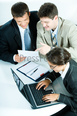 Фотография на тему Два бизнесмена обсуждают план, а женщина набирает документ
