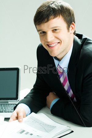 МОлодой бизнесмен сидит на рабочем месте и смотрит в камеру
