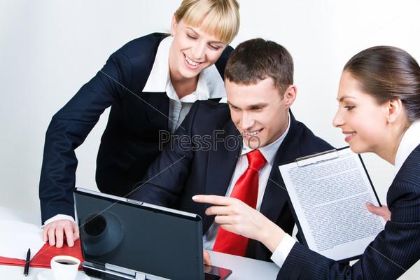 Уверенные партнеры смотрят на экран ноутбука с улыбками