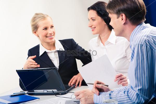 Приятная деловая женщина указывает на монитор ноутбука