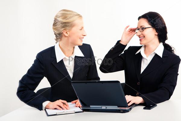 Счастливые женщины в костюмах смотрят друг на друга с улыбками