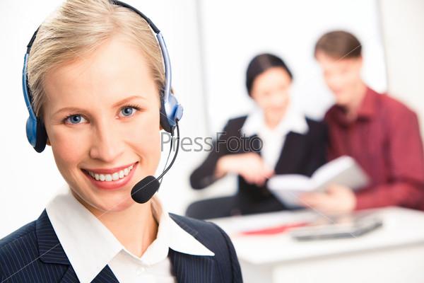 Красивая блондинка с головным телефоном смотрит в камеру