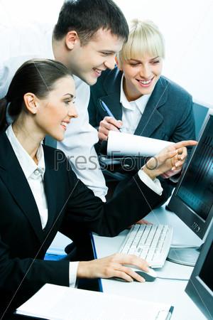 Трое студентов сидят за столом напротив компьютера