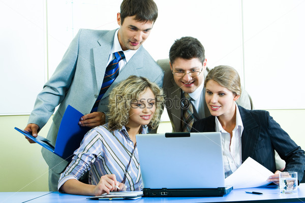 Уверенные люди смотрят на экран ноутбука на встрече в офисе