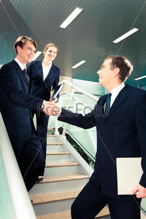 Рукопожатие деловых партнеров при встрече на лестнице