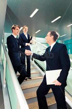 Рукопожатие деловых партнеров в офисном здании