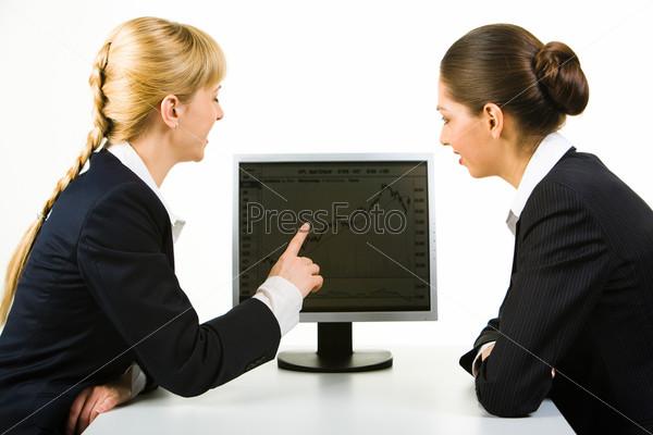 Фотография на тему Две деловые женщины сидят у компьютера за столом