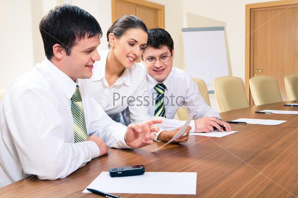 Двое мужчин сидят за столом и смотрят на документ в руке секретаря