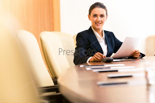 Сидящая деловая женщина с документами смотрит в камеру