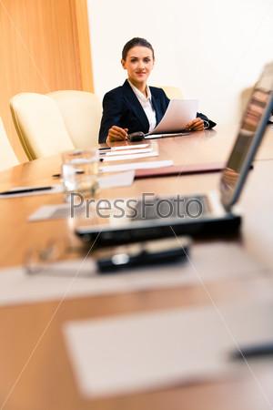 Фотография на тему Уверенная деловая женщина сидит в дальнем конце кабинета