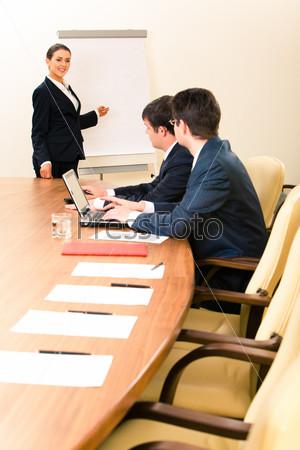 Женщина читает лекцию деловым людям и указывает на доску