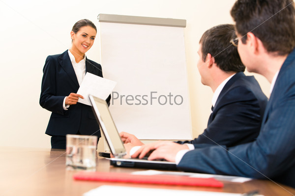 Менеджер стоит у доски и смотрит на бизнесменов