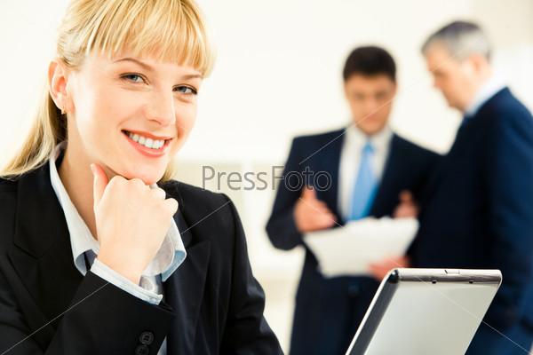 Лицо улыбающейся женщины в рабочей обстановке