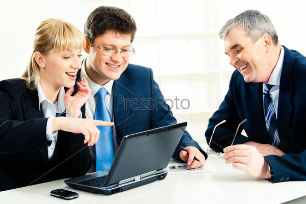Группа деловых людей сидит у ноутбука и смотрит на его экран