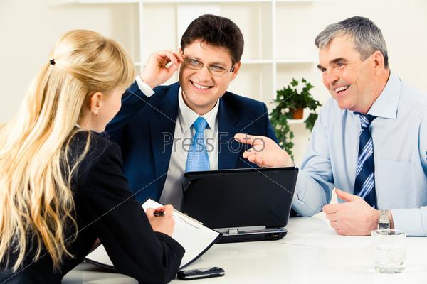 Трое успешных деловых людей общаются на рабочем собрании