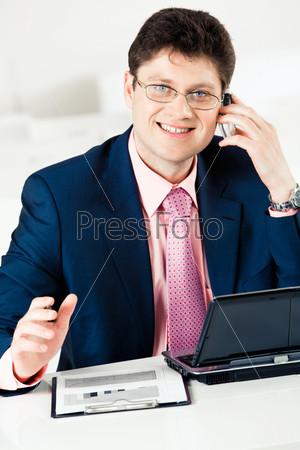 Умный бизнесмен звонит по телефону и смотрит в камеру