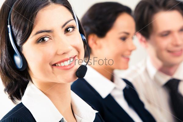 Красивая девушка с головным телефоном на фоне двух говорящих людей