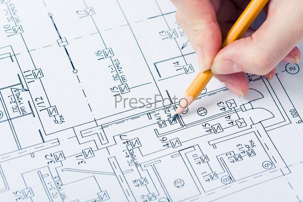 Эскиз таблицы, над которым находится рука с карандашом