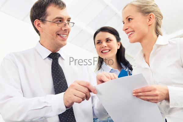 Деловая команда работает с бумагами в офисе