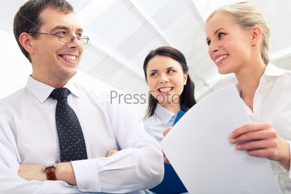 Photo of confident boss interacting with two businesswomen in the office