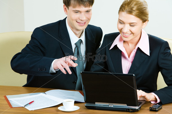 Portrait of businessman and woman sitting at table and working on laptop