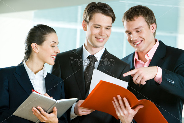 Image of business team in suits discussing papers in man's hand