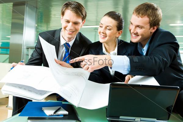 Группа деловых людей смотрит на новый план и обсуждает его в офисе