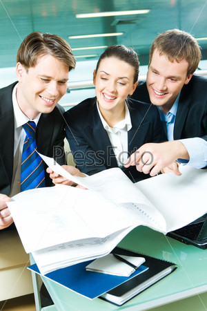 Vertical image of three people sitting in the office and discussing documents