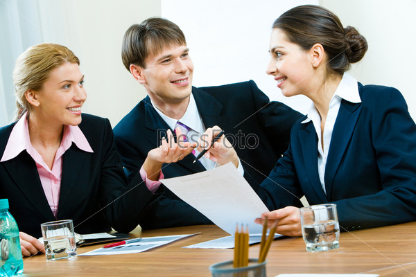 Portrait of white-collar workers sitting at table and working with documents in the office
