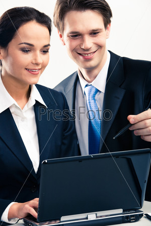 Portrait of businessman showing a computer work to co-worker