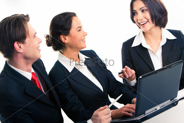 Conversation of three confident businesspeople sitting at the table