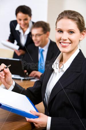 Портрет симпатичной секретарши с ручкой и бумагой в руках